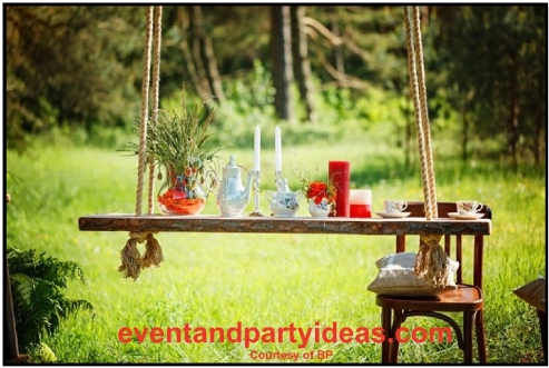 outdoor, party, rustic swing, outdoor swing as a table with silver teapot, silver candlestick, and tea cups. eventandpartyideas.com