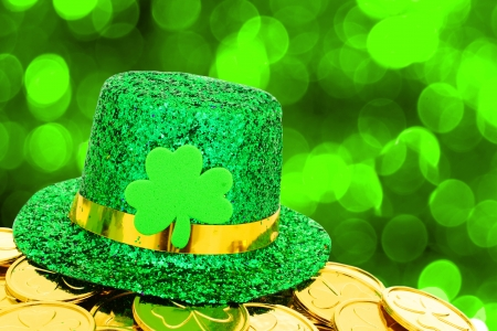 17681063 - shiny st patricks day hat and gold coins on green twinkling background